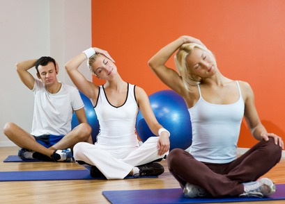 Group of people doing yoga exercise (focus on woman in the middl