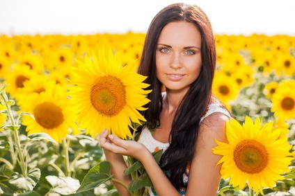 Beautiful young woman on the sunflowers field