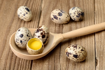 Quail eggs in wooden spoon