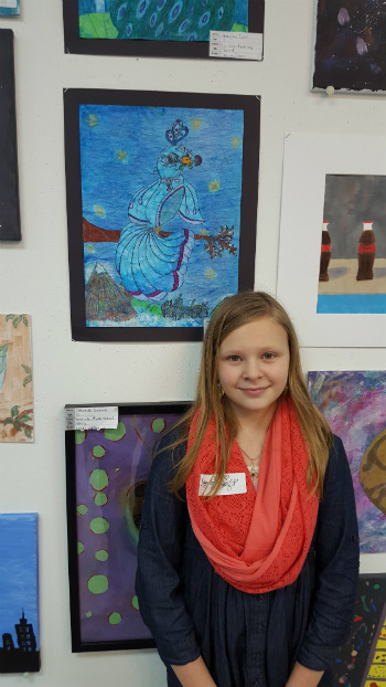 Taylor Daft pictured with her artwork (the blue bird in the background)