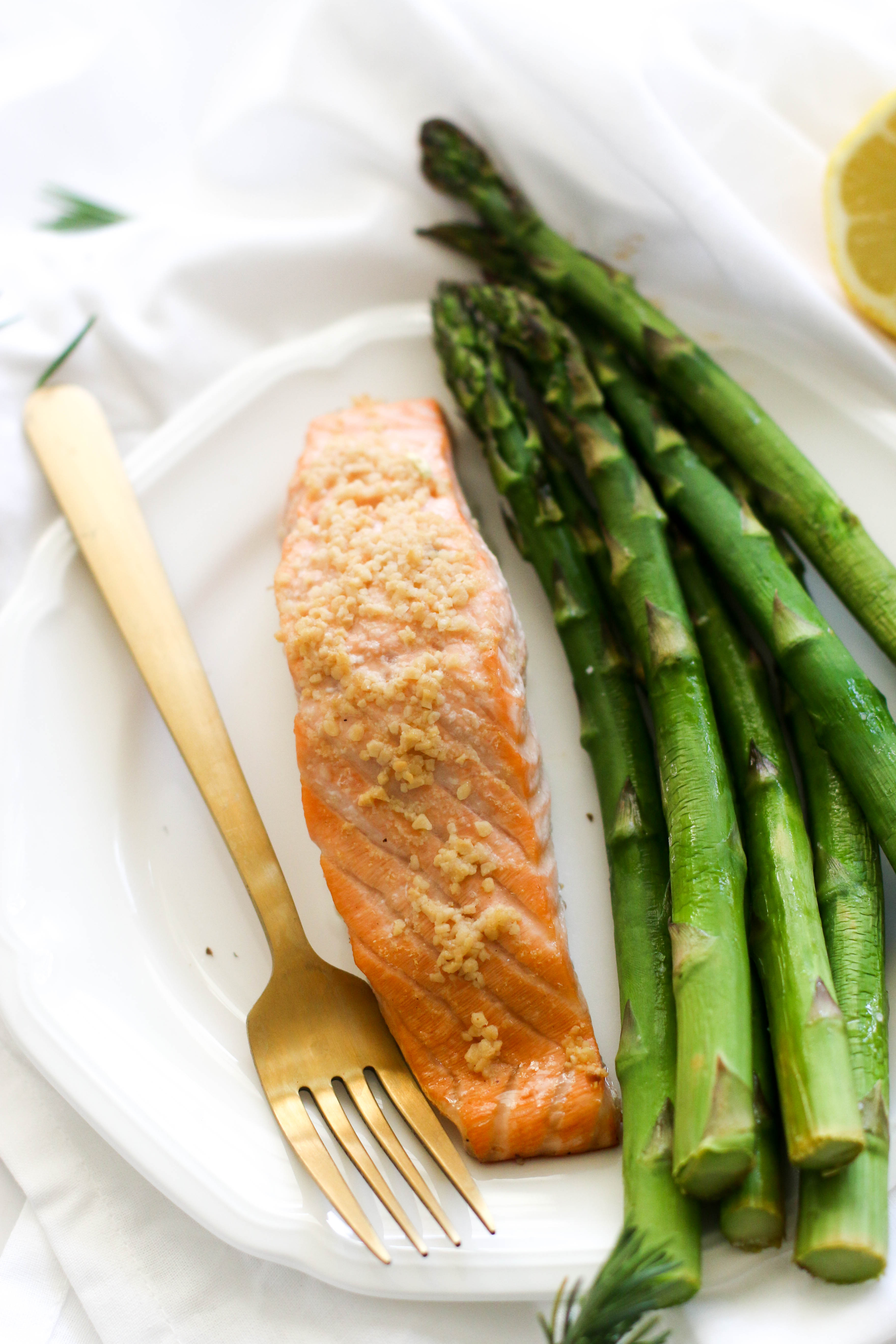 This one pan lemon garlic salmon & asparagus dish is paleo, gluten free, and a great 20 minute dinner. It's filled with healthy fats, fresh produce, and when served with a side of carbs, makes for a balanced, healthy dinner!