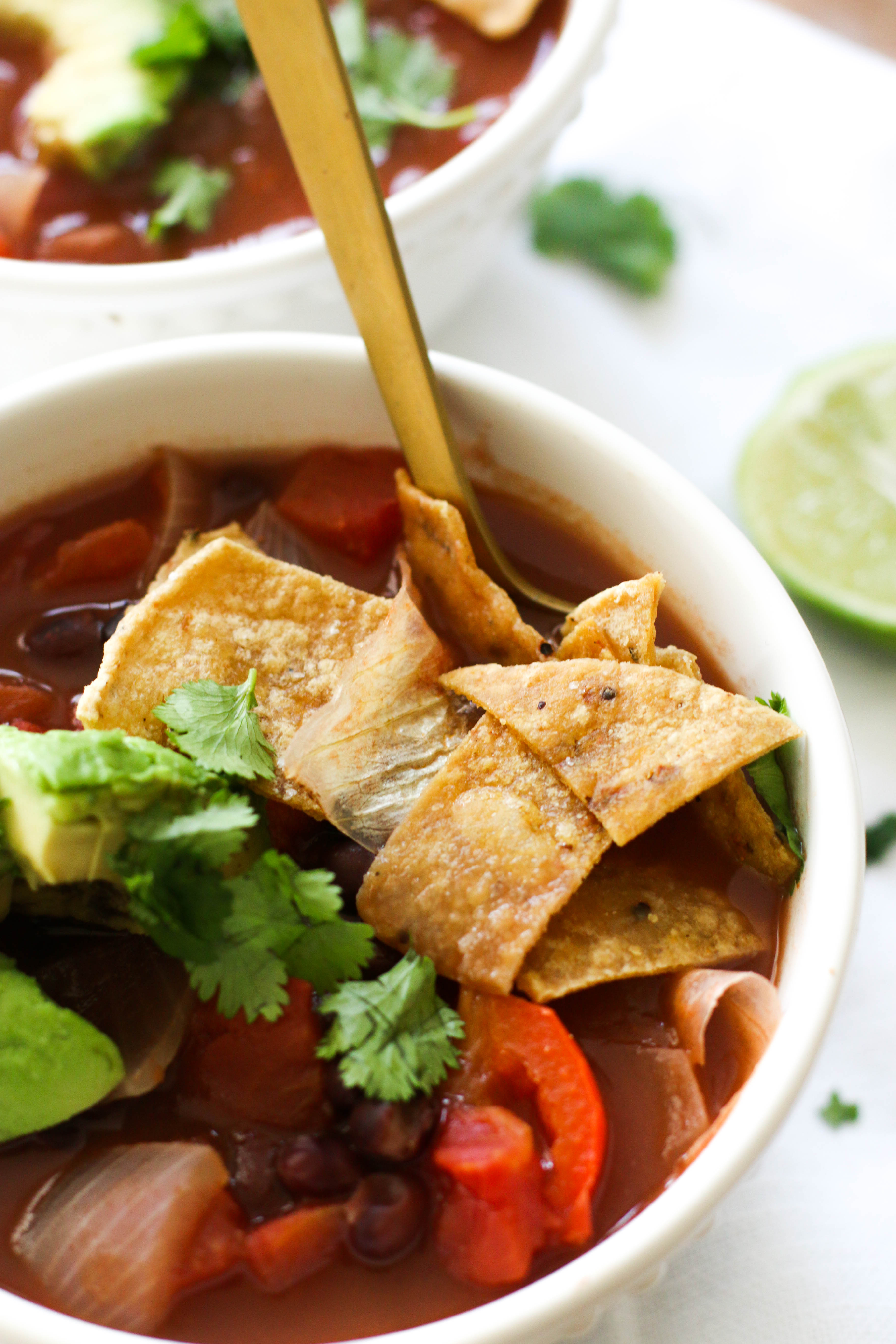 This black bean tortilla soup is vegan, gluten free, and filled with protein! It's ready in under an hour and pairs well with homemade tortilla chips, making it the perfect quick meal.