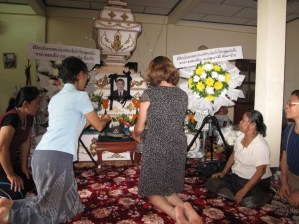 Laying down gifts in front of the coffin of the deceased before fire burial