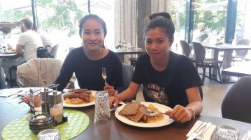 "Ms Moukdala Keomixai and Ms Siliphone Arnousavanh enjoy traditional German ""Bratwurst [sausage] and Sauerkraut"" in the company restaurant of BHS Corrugated"