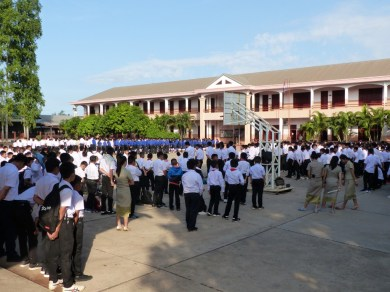 Pupils and teachers stand in front of the main school building...