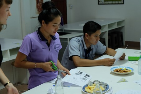 While Mr Sackbong Boulapane studies the instructions, Ms Khamsee Thanbounhueang starts to craft her booklet.
