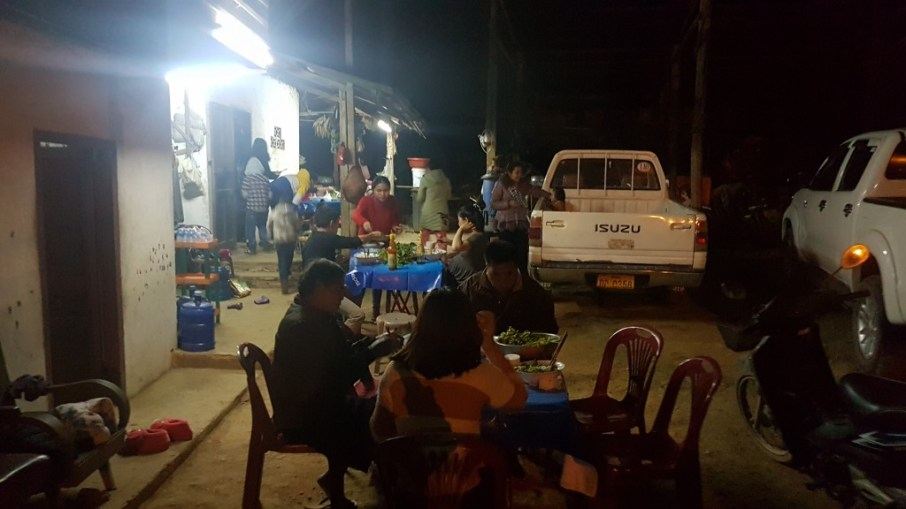 ... family and friends enjoy their dinner together in aunt Thay's yard.