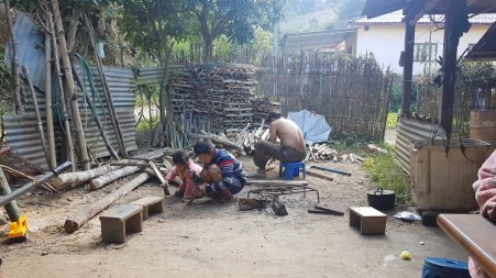 One of Khamsee's friends and his two sons work on their firewood.