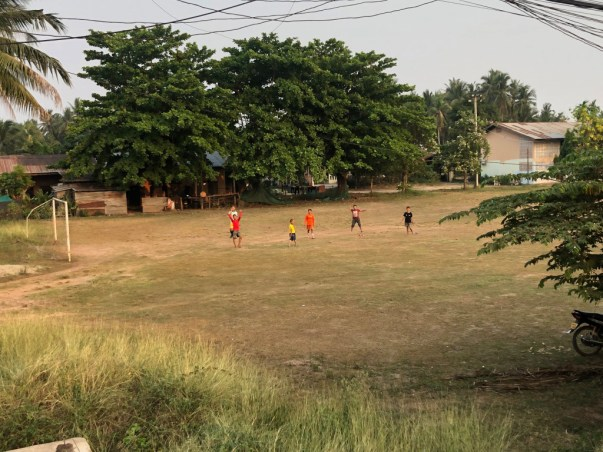 Children on a football pitch in the periphery of Vientiane greet us while we're riding past.