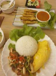 Rice with stir-fried vegetables and omelett and at the top: Chicken Satay sticks