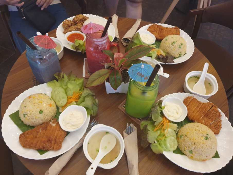 A table full of delicious chicken dishes, smoothies, and side soup (obligatory in Laos)