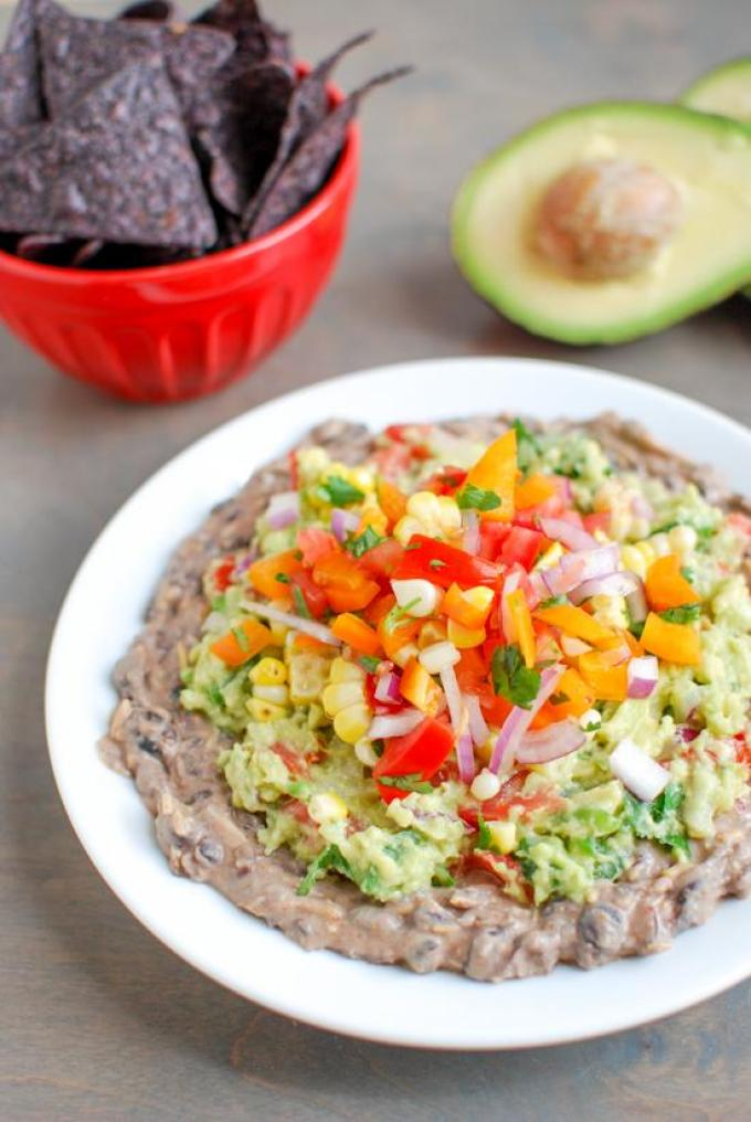 This Mexican Layer Dip is easy to make and full of flavor! With layers of spicy black bean dip, homemade guacamole and fresh corn salsa it's the perfect party appetizer or snack!
