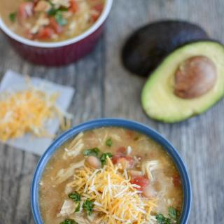 Two bowls of white chicken chili with an avocado and cheese and cilantro