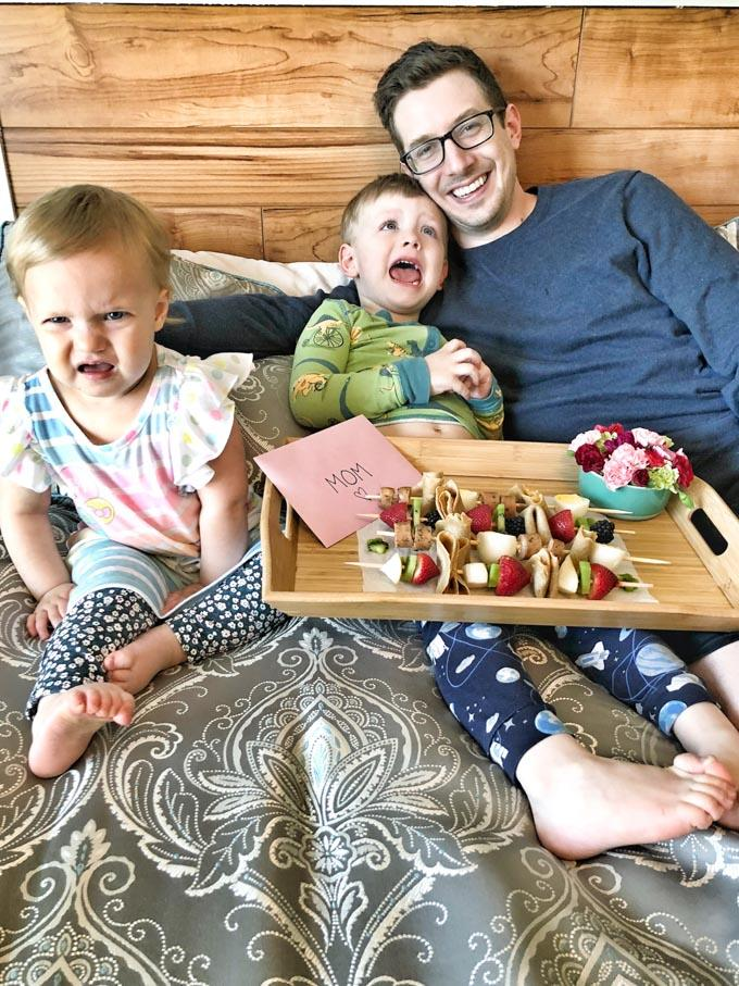 Family serving crepe kabobs to mom in bed for Mother's Day