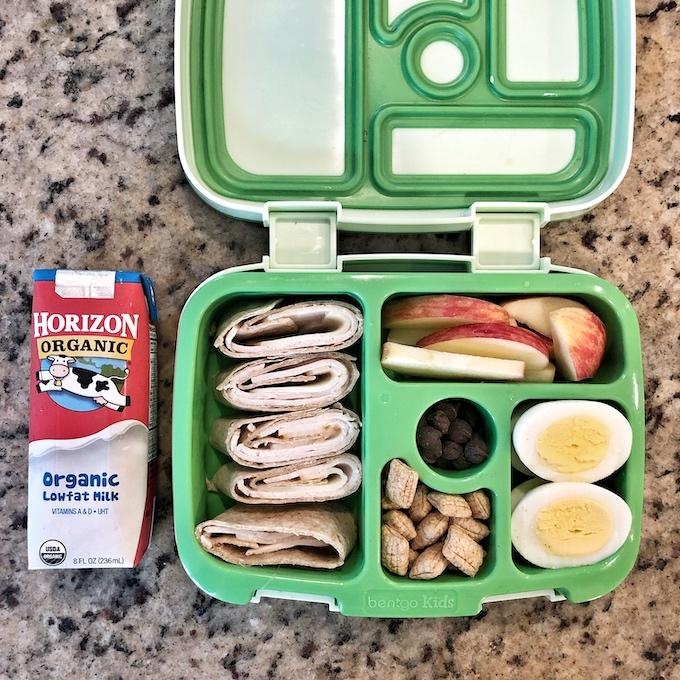 Packed lunch with horizon organic shelf stable milk, turkey rollup, apple, barbaras puffins, hard boiled eggs
