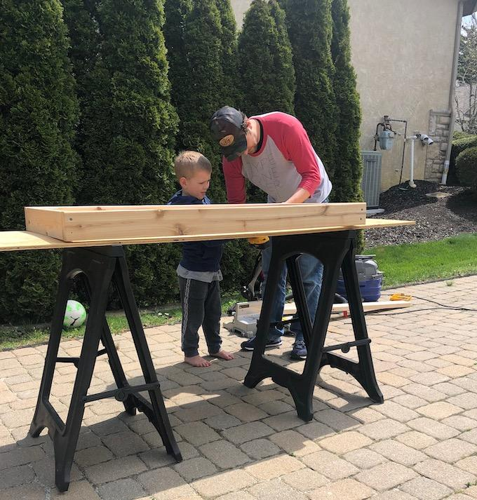 man and son building mud kitchen cooktop