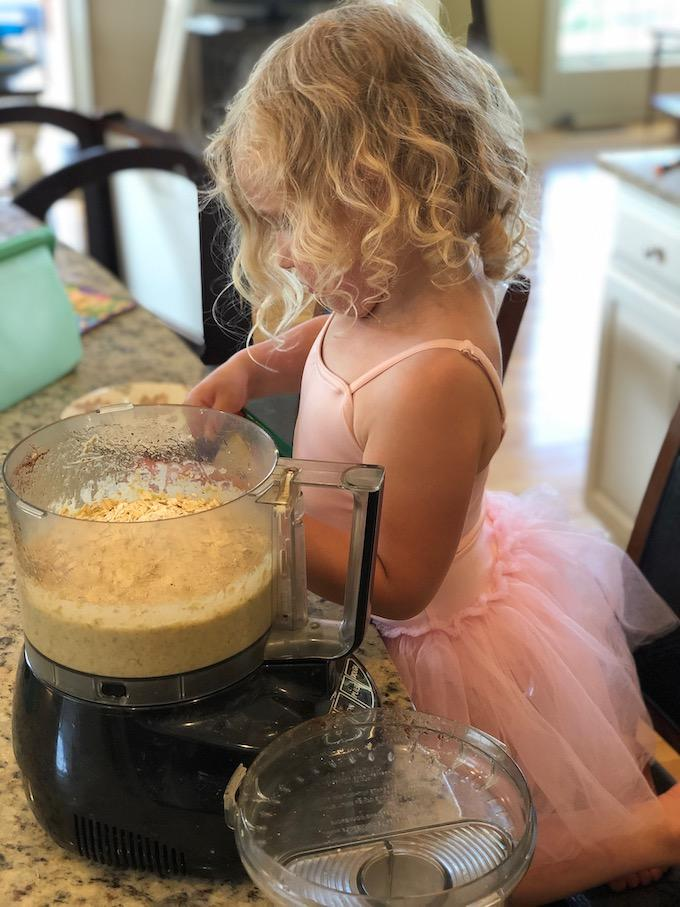 toddler making muffins with a food processor
