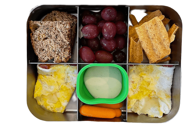 kids lunch with banana bread, egg wrap, carrots with ranch, sun chips and grapes