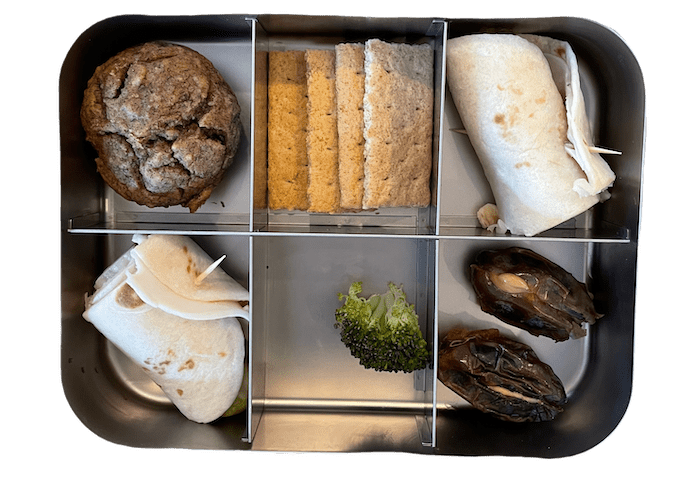 elementary lunch box with lentil banana muffin, turkey roll up, dates with peanut butter and graham crackers