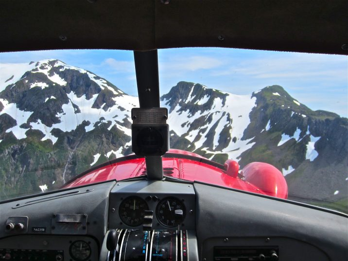 photo of view from cockpit of airplane of snow-capped mountains