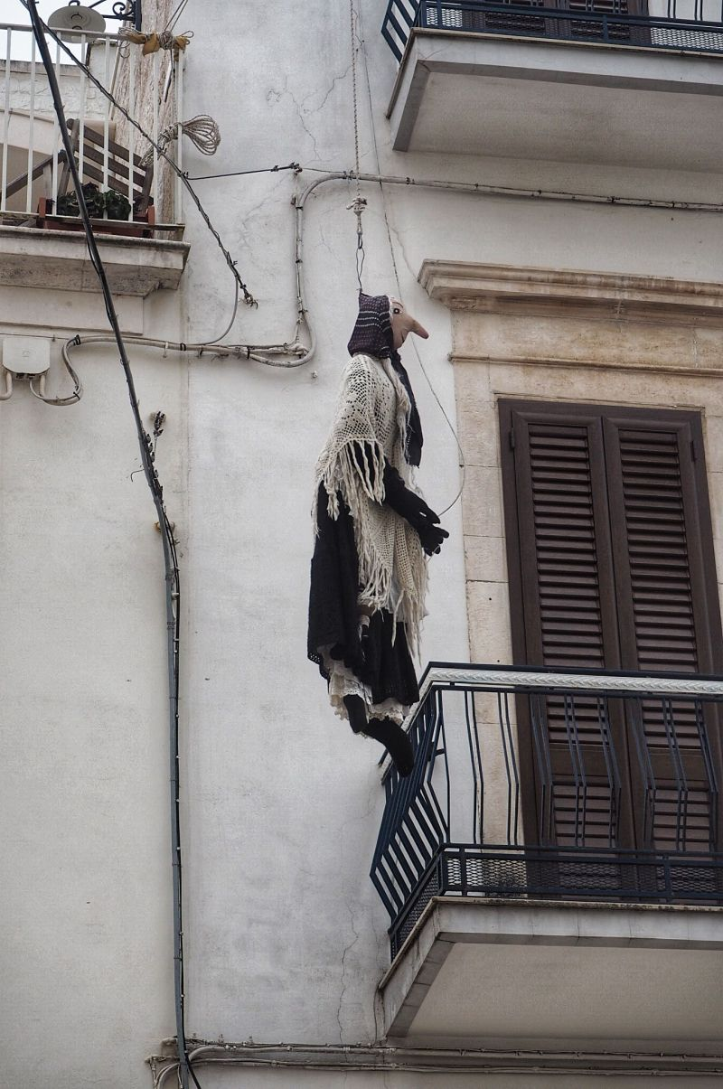 Puglia Quarandone puppets hanging from rope in the street