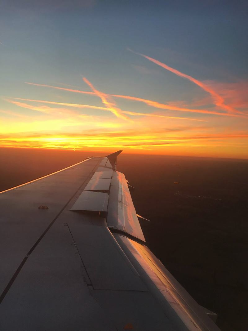 Sunset plane window seat view - this post contains affordable luxury travel for less, including travel hacks for affordable air travel