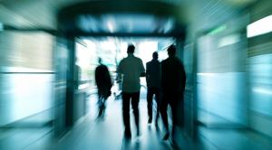 Silhouettes of walking people in a subway corridor, blurred motion, rear view, back lit