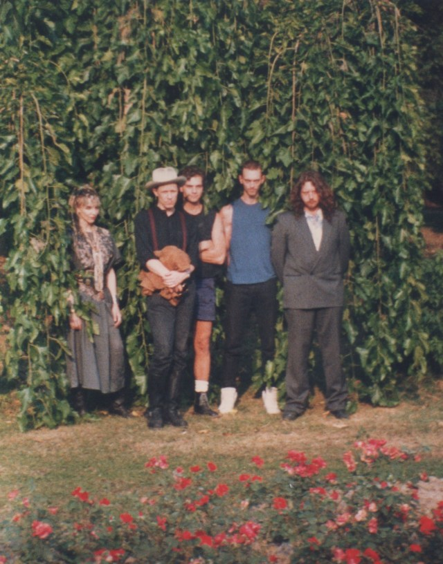 BAND POSE IN FRONT OF HIGH GARDEN