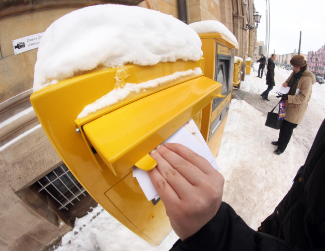 A man posts a letter in the snow in Magdeburg