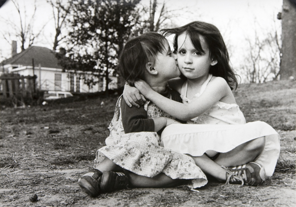 Two young girls seated one kissing others cheek-2