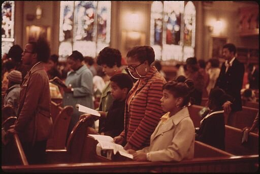 John H. White, 1945-, Photographer: WORSHIPPERS AT HOLY ANGEL CATHOLIC CHURCH ON CHICAGO'S SOUTH SIDE. IT IS THE CITY'S LARGEST BLACK CATHOLIC CHURCH. THE PASTOR IS FATHER GEORGE H. CLEMENTS, A LEADER IN THE BLACK COMMUNITY, National Archives at College Park, Public domain, via Wikimedia Commons.