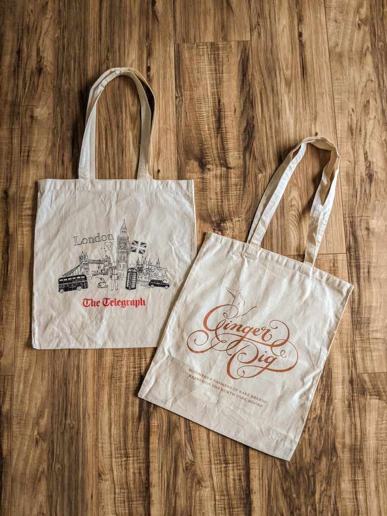 tote bags from ginger pig butcher and telegraph newspaper in London
