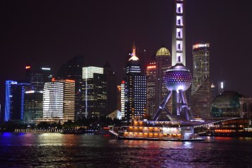 Shanghai - Pudong skyline by night and its riverboat