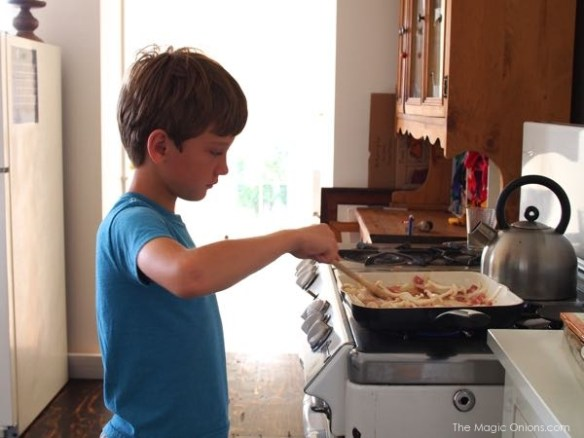 photo of boy cooking bacon and egg pie
