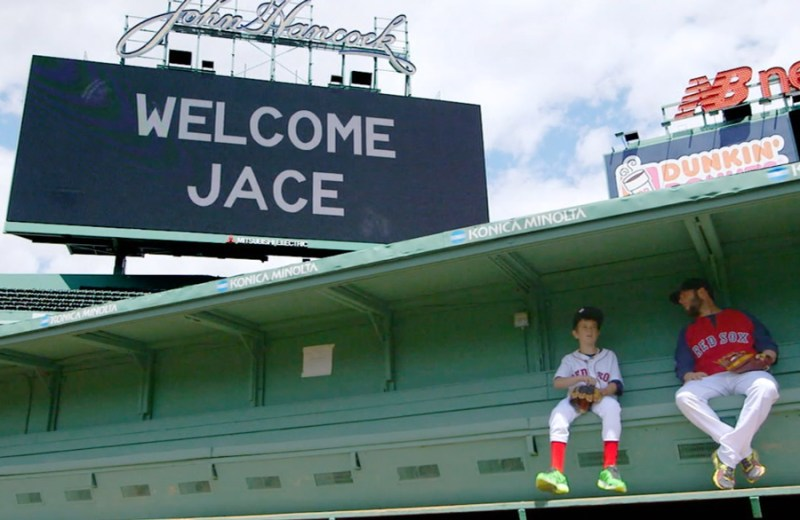 """Make-A-Wish Kid Jace Andrews and Dustin Pedroia sit below """"Welcome Jace"""" Sign at Fenway Park"""