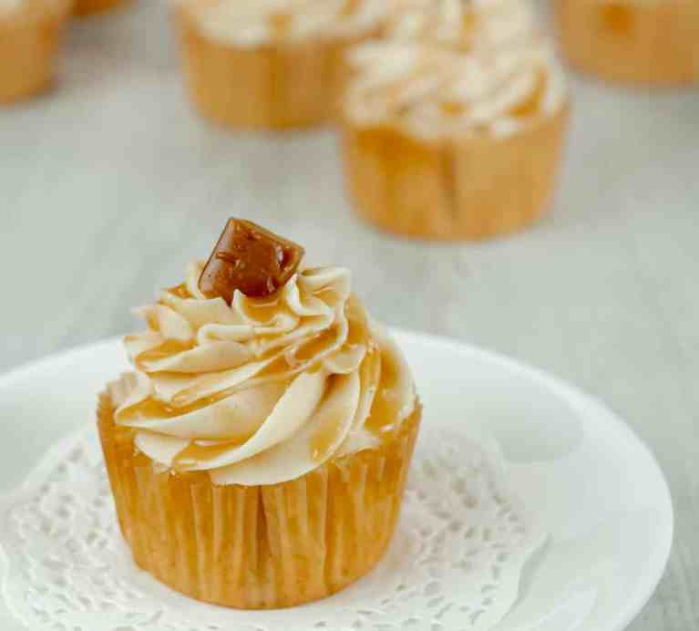 homemade caramel drizzled on brown sugar buttercream frosting with a vanilla cupcake base