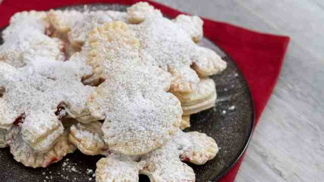 Christmas hand pies cookie cutter snowman snowflake christmas tree red napkin powdered sugar black plate