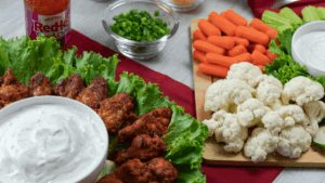 game day party food ideas wings lettuce carrots cauliflower vegetables red background