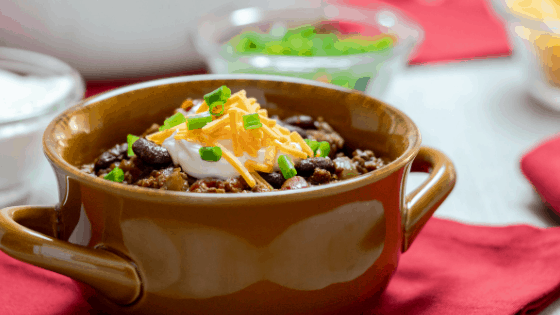 Instant Pot Homemade Chili beans tomatoes peppers cheese scallions sour cream brown bowl red napkin
