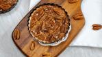 mini pecan pies serving board pecan pieces tart pan doilies white napkin gray background