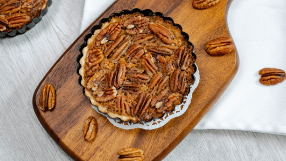 mini pecan pies serving board pecan pieces tart pan doilies white napkin gray background