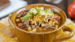 instant pot taco soup in brown bowl with handles. Tortilla chips, and topped with shredded cheese and fresh avocado.