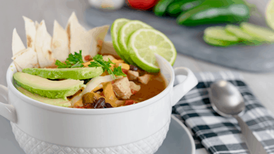 Instant Pot Chicken Tortilla Soup in white bowl black and white checkered napkin limes and avocado