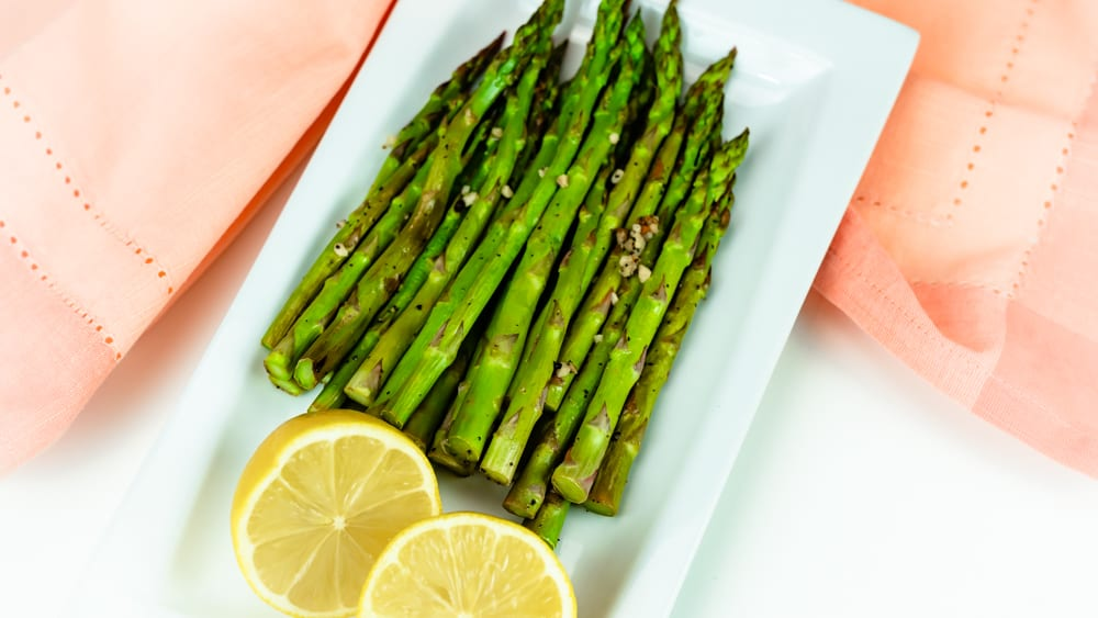 Lemon Oven-Roasted Asparagus on white plate with a sliced lemon