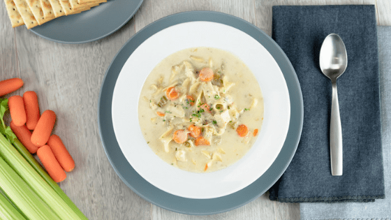 Instant Pot Creamy Chicken Noodle Soup with gray plate and brushed spoon