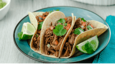 Instant Pot Beef Barbacoa Tacos served with pico de gallo, fresh sliced limes, and cilantro