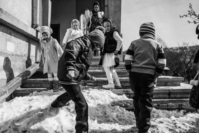 Bambini giocano all'uscita della messa domenicale.  Breb, Maramures, Romania, aprile 2015.