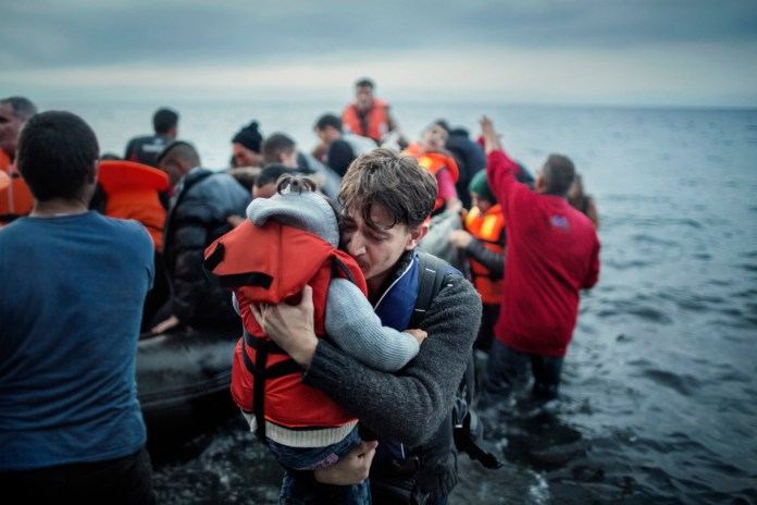 Lesbos. Greece. Oct. 21, 2015.  A  father hugs his young daughter as they land on the Greek island of Lesbos,  after crossing the Aegean sea from the Turkish coast  He later said they were afraid during the trip because of the bad weather.According to UNHCR, approximately 850,000 refugees and migrants, including children, arrived in Greece by sea in 2015. Of these, just over 500,000 landed on Lesbos, a Greek island around eight nautical miles from the Turkish coast.  Although at the centre of migration flows, Lesbos had nothing to offer the mainly Syrian, Afghan and Iraqi refugees, asylum seekers and migrants who arrived there. Once they reached Europe's beaches, they were welcomed with a long trek across the island's mountainous interior, followed by days and nights spent in crowded refugee camps, where not even a place in a tent was guaranteed and where basic amenities such as toilets and showers were lacking. © Alessandro Penso