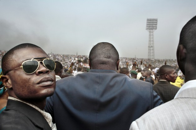"Guy Tillim Jean-Pierre Bemba surrounded by his body guards walks into an election rally in central Kinshasa, 2006 dalla serie ""Congo Democratic"" stampa inkjet ai pigmenti su carta cotone 49,5 x 72 cm © l'artista"