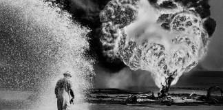Spray chimici proteggono questo pompiere dal calore delle fiamme. Pozzi di petrolio, Greater Burhan, Kuwait, 1991. © Sebastião Salgado /Amazonas Images/Contrasto